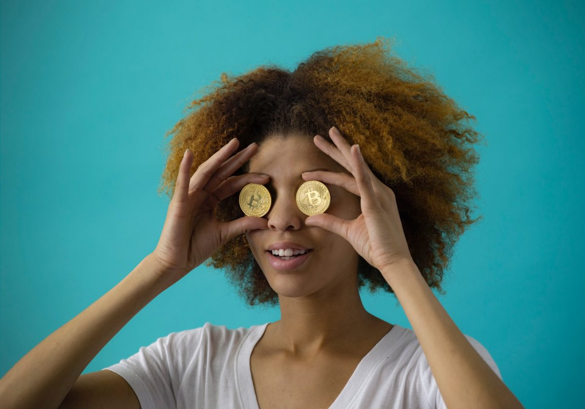 Girl holding two bitcoins in front of eyes